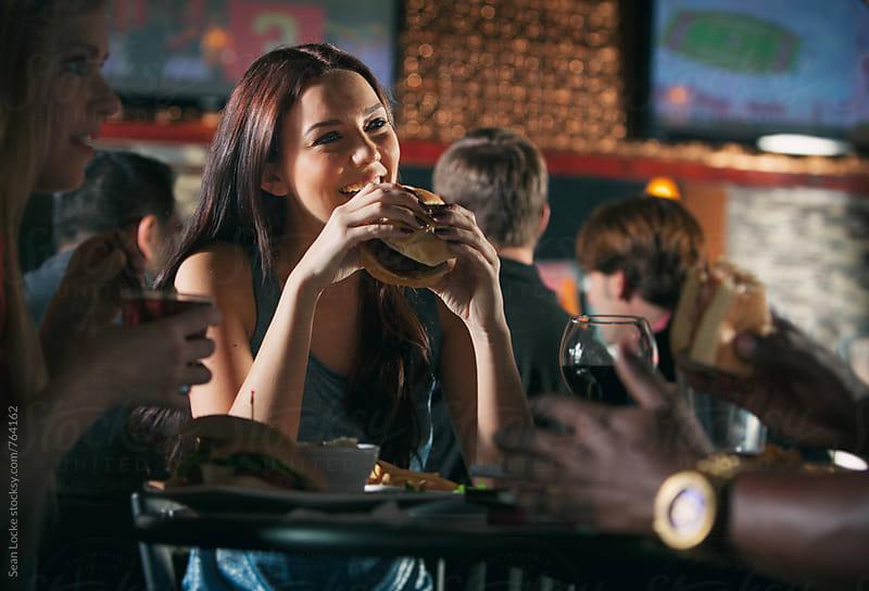 Bar: Pretty Girl Eats Giant Burger At Restaurant  by Sean Locke for Stocksy United
