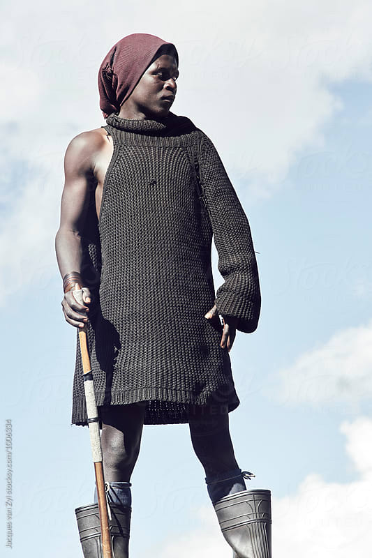 A portrait of a young black Basotho shepherd against a clouded sky. by Jacques van Zyl for Stocksy United