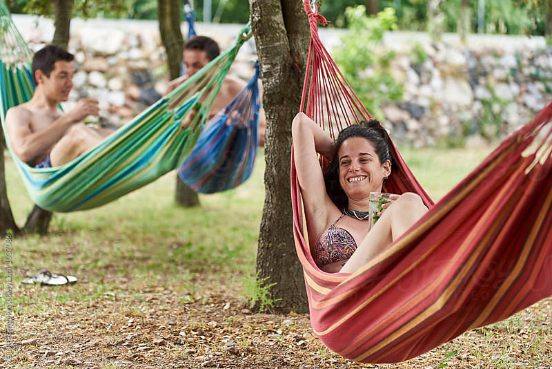 Smiling woman in bikini relaxing in hammock with drink by Guille Faingold for Stocksy United