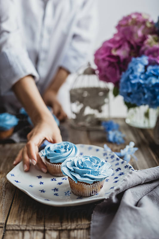 Woman is taking blue cupcake by Tatjana Zlatkovic for Stocksy United