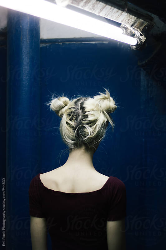 Anonymous blonde female model in front of the blue door in the basement by Evil Pixels Photography for Stocksy United