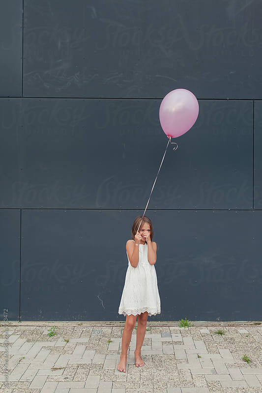 Smiling little girl with a single pink balloon against a dark wall by Cindy Prins for Stocksy United