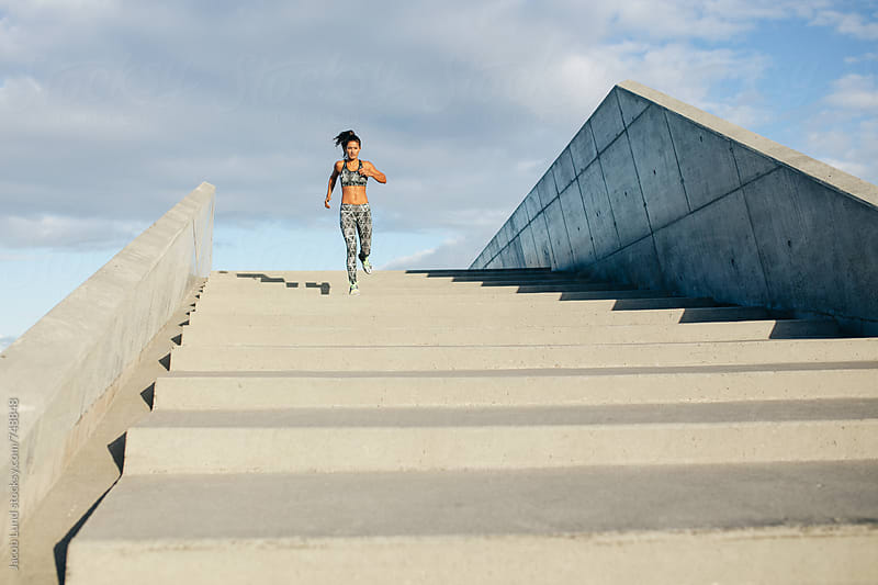Woman running down stairs by Jacob Lund for Stocksy United
