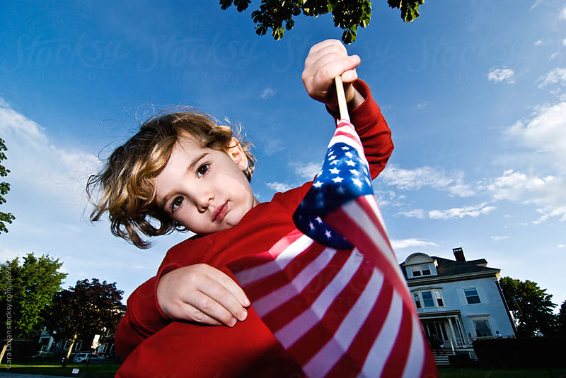 Boy waves an American Flag on the 4th of July by Cara Slifka for Stocksy United