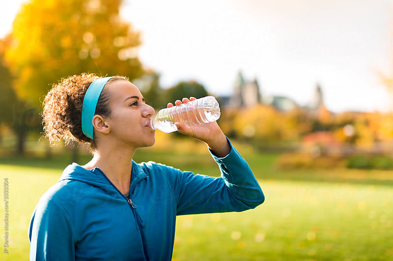 Young Woman Drinking from Water Bottle While Jogging In Ottawa in Autumn by JP Danko for Stocksy United