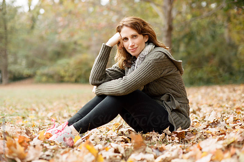 A beautiful woman sitting in a bed of leaves by Jakob for Stocksy United