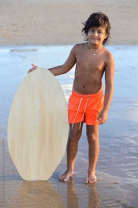 Boy holding a slide surf board by Marta Muñoz-Calero Calderon for Stocksy United