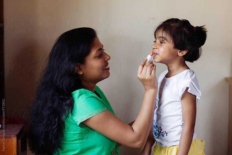 Mother applying lipstick on her daughter's lip by Saptak Ganguly for Stocksy United