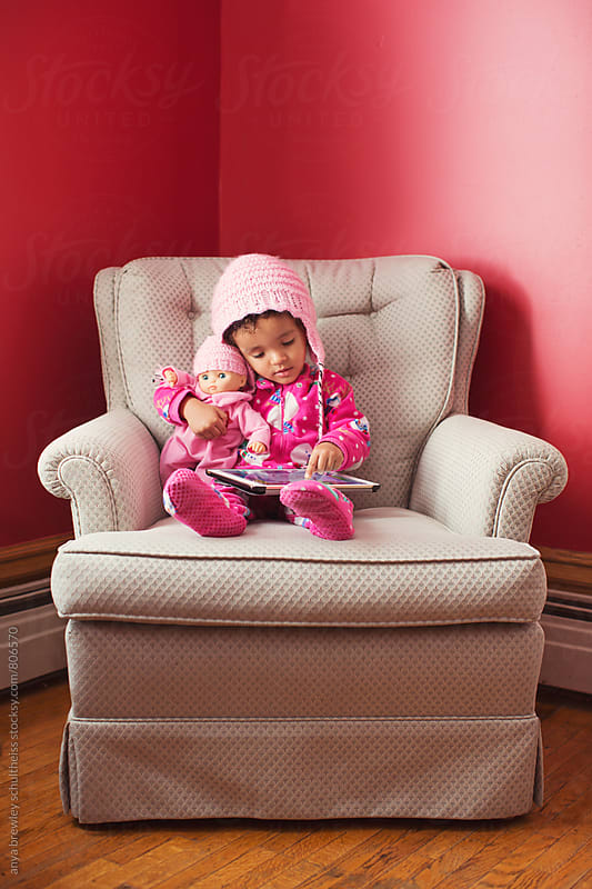 Toddler girl with pink hat holding and cuddling her baby doll with a matching pink hat by anya brewley schultheiss for Stocksy United