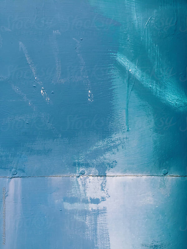 Blue and turquoise colored paint covering graffiti on metal warehouse wall, close up by Paul Edmondson for Stocksy United