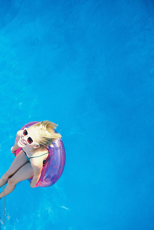 blonde girl with white sunglasses in pink floatie in blue pool by wendy laurel for Stocksy United