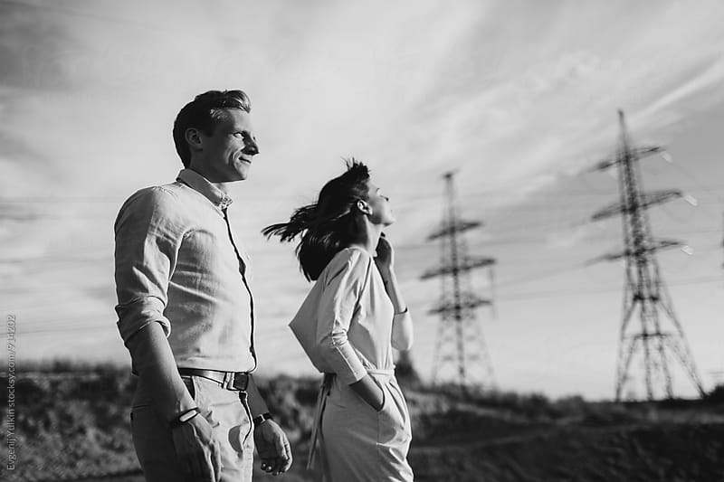 Young couple beside the power tower by Evgenij Yulkin for Stocksy United