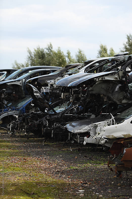 Wrecked cars piled up, at a acar scrapyard by Marcel for Stocksy United