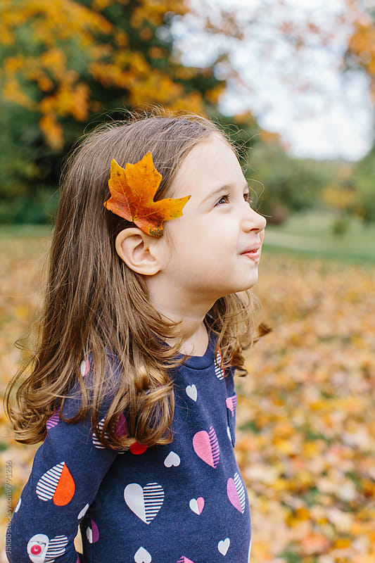 Cute young girl with a leaf behind her ear by Jakob for Stocksy United