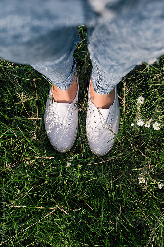 Female tennis shoes on grass by Danil Nevsky for Stocksy United