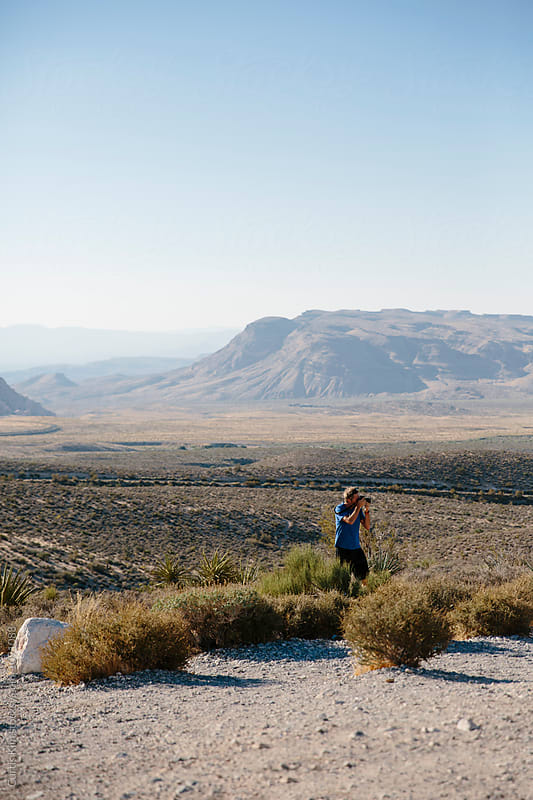 Man taking photos in the desert by Curtis Kim for Stocksy United
