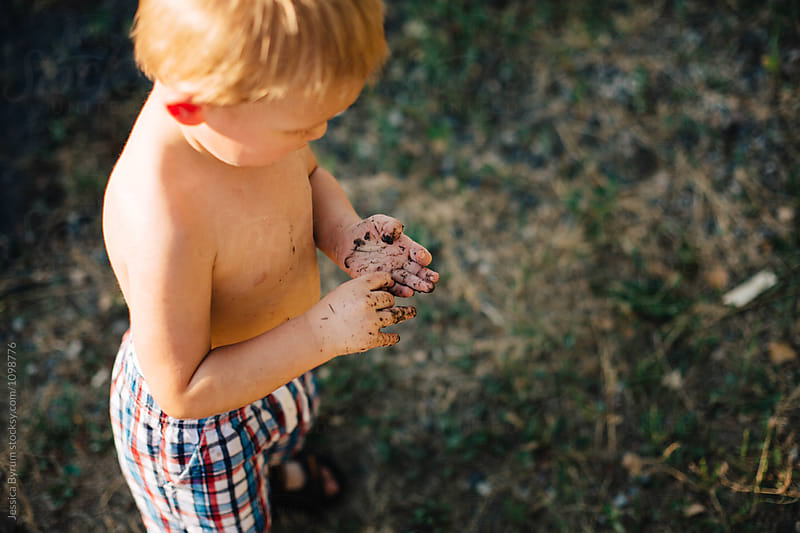 Blonde toddler boy with mud on his hands. by Jessica Byrum for Stocksy United