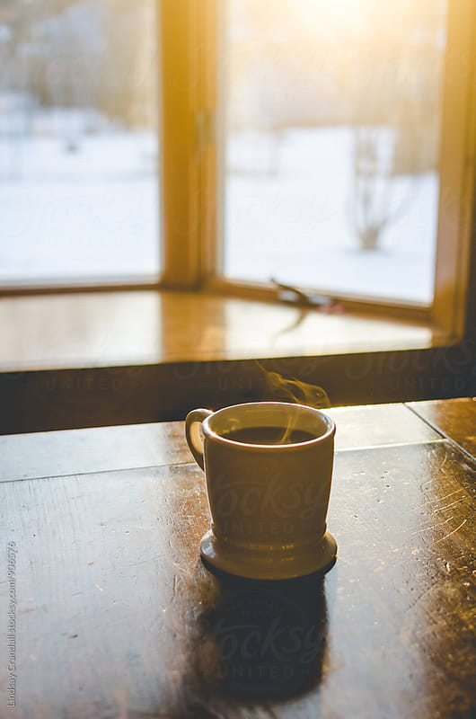 Steaming cup of coffee on a sunny winter morning by Lindsay Crandall for Stocksy United
