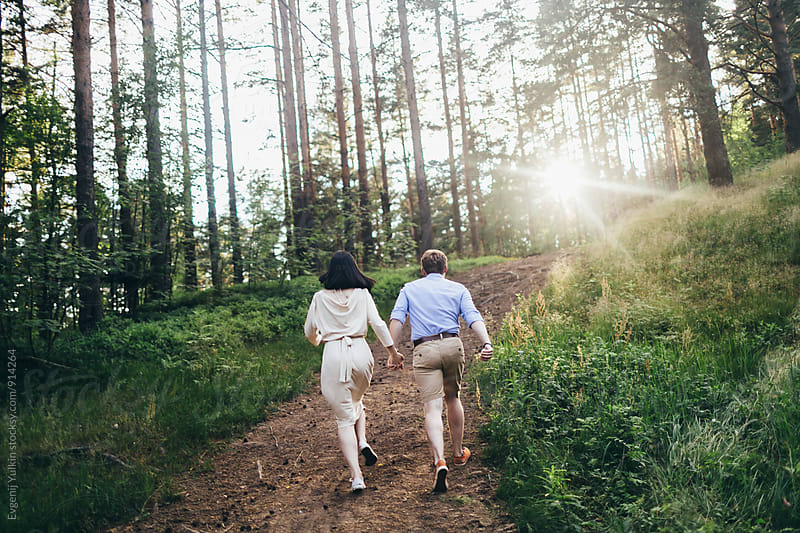 Couple running along the forest road by Evgenij Yulkin for Stocksy United