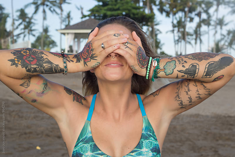 Beautiful tattooed woman hiding her eyes by Jovo Jovanovic for Stocksy United