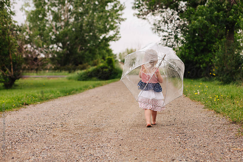 Cute toddler girl in an American flag dress walking in driveway with a big umbrella. by Jessica Byrum for Stocksy United