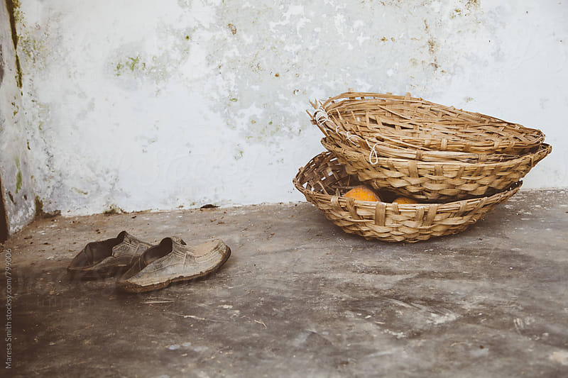 Shoes and a basket against a rustic wall by Maresa Smith for Stocksy United