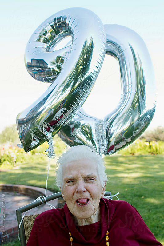 Woman turns 90 years old and sticks tongue out to camera by Tana Teel for Stocksy United