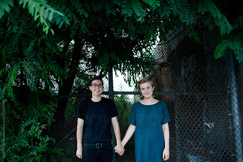 Attractive lesbian couple holding hands, facing camera by Jennifer Brister for Stocksy United