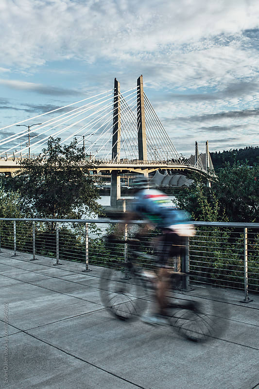 Bicyclist Riding On Riverside Path Towards Bridge by Evan Dalen for Stocksy United