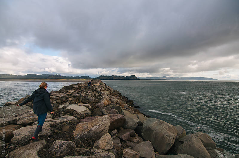 woman walks along jetty back toward shore by Margaret Vincent for Stocksy United