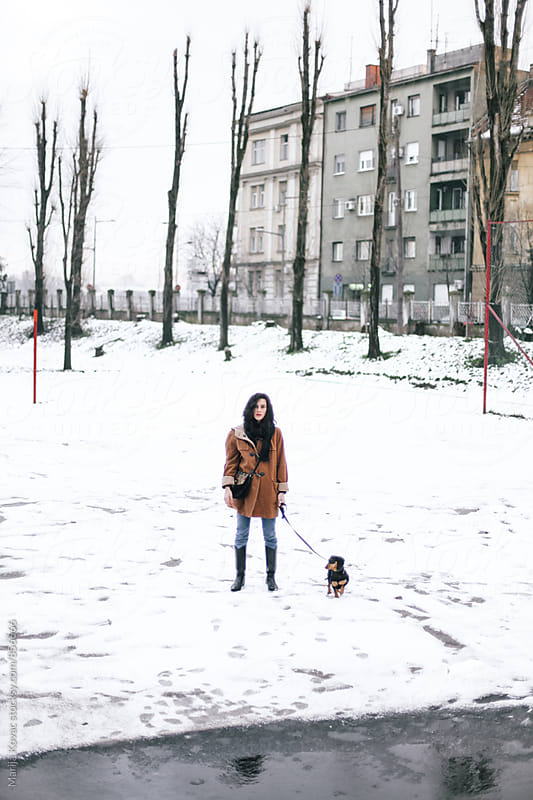 Stylish woman with a black dog outdoor, winter day  by Marija Kovac for Stocksy United