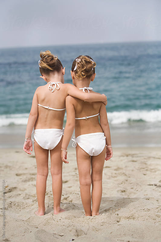 Back View Of Young Twin Girls On Beach Hugging by Dina Giangregorio for Stocksy United