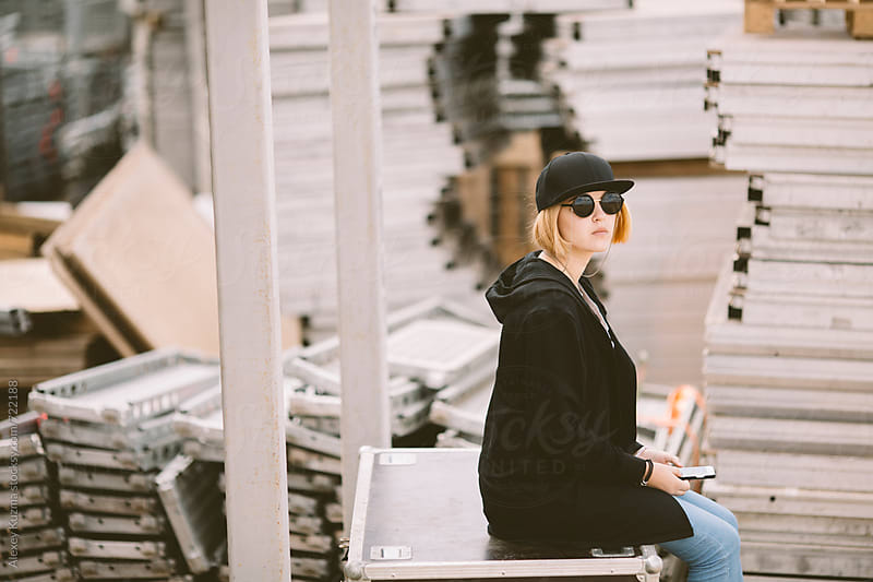 cool teen girl near industrial crates by Alexey Kuzma for Stocksy United