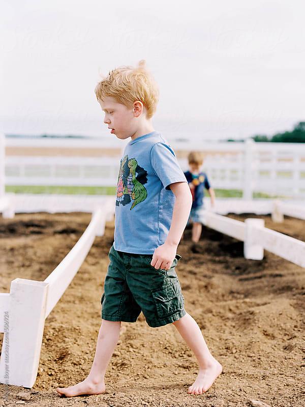 Boy walking in a garden by Meghan Boyer for Stocksy United