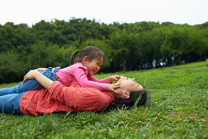 happy little asian girl playing with her mother outdoor in the park by Bo Bo for Stocksy United