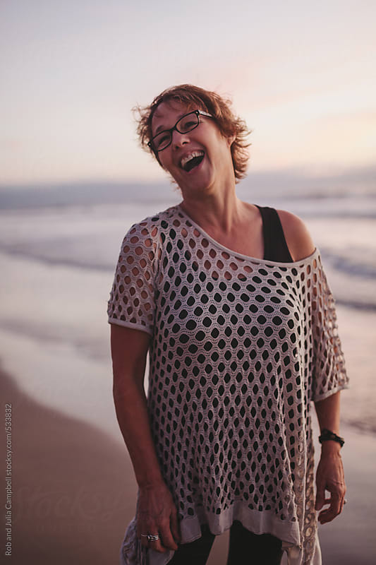 Fun middle aged woman laughing outside on ocean beach at sunset by Rob and Julia Campbell for Stocksy United