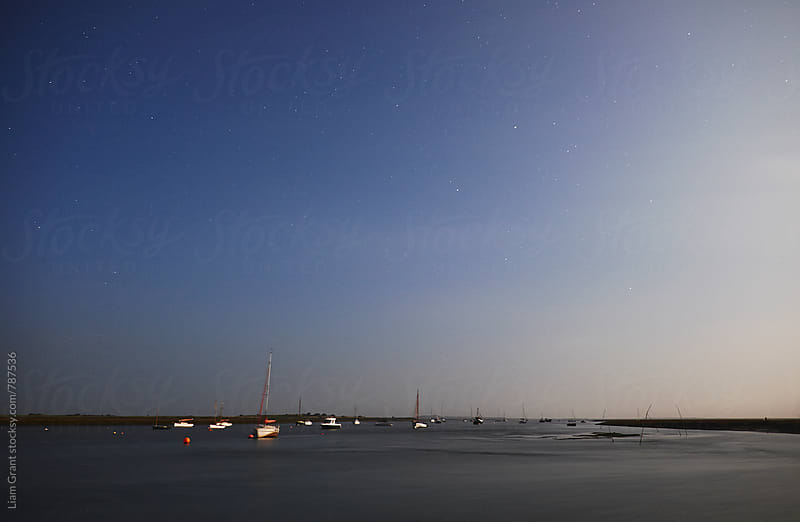 Moonlight on boats under a star filled sky. Brancaster Staithe, Norfolk, UK. by Liam Grant for Stocksy United