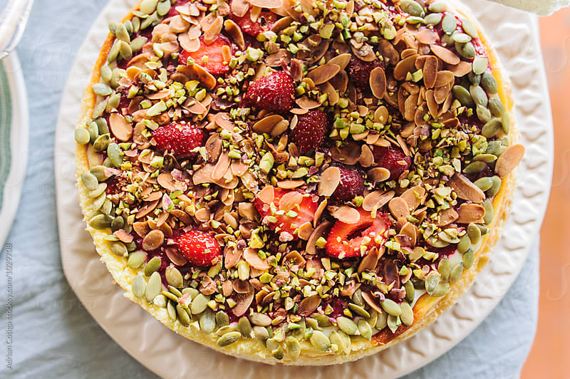 Delicious tart with strawberry and nuts by Adrian Cotiga for Stocksy United