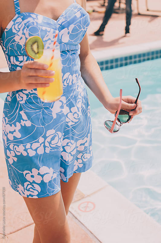 Girl Holding a Drink by the Pool by Gabrielle Lutze for Stocksy United