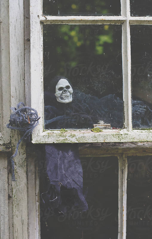 A ghoul at the window of a derelict building by Helen Rushbrook for Stocksy United