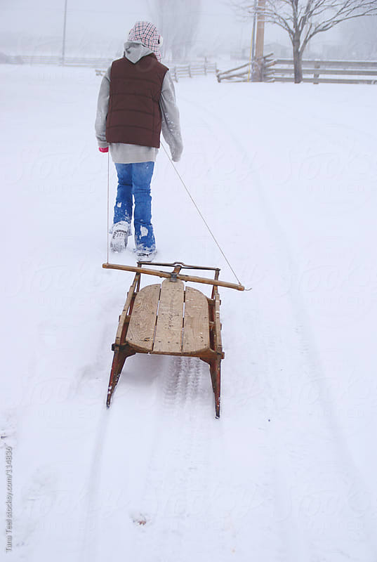 A young girl pulls an old vintage wooden sled up a snowy slope by Tana Teel for Stocksy United