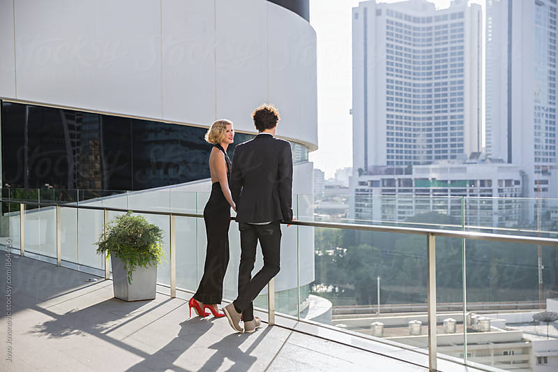 Stylish young couple standing on a balcony together and looking at the city skyline  by Jovo Jovanovic for Stocksy United