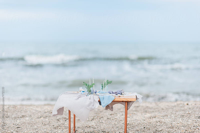 Table setup on the beach on summertime; Table for two on the beach by Adrian Cotiga for Stocksy United