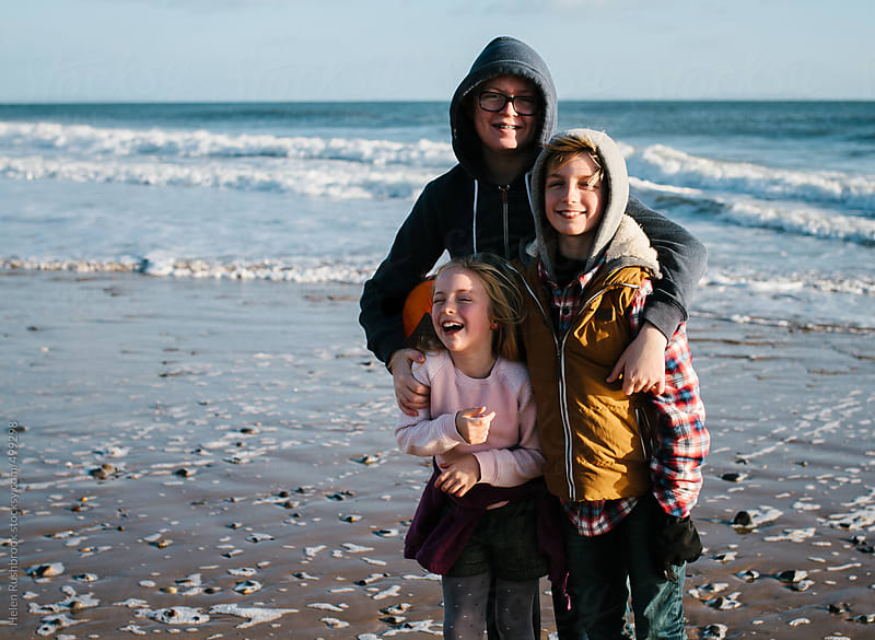 3 siblings on a beach, laughing. Two are looking at camera. by Helen Rushbrook for Stocksy United