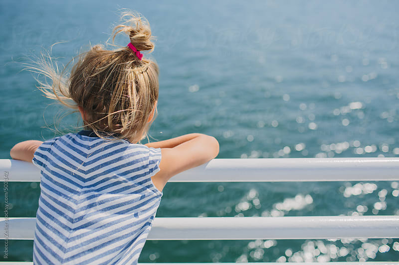 a girl in a striped dress stands on a ferry, looking out over the water by Rebecca Zeller for Stocksy United