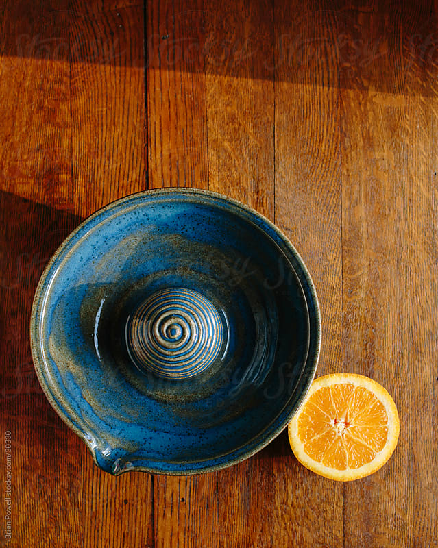 a blue juicer ready to juice an orange by Brian Powell for Stocksy United