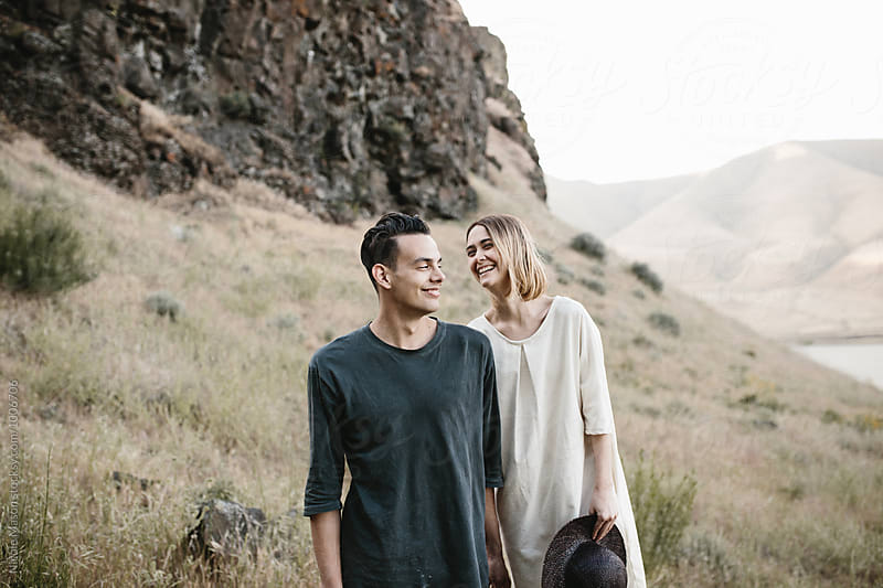 young fashionable couple laughing together in desert by Nicole Mason for Stocksy United