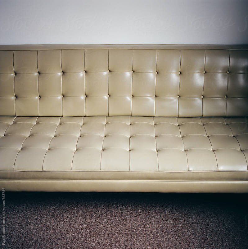 Retro couch in minimalist and modern hotel room by Paul Edmondson for Stocksy United