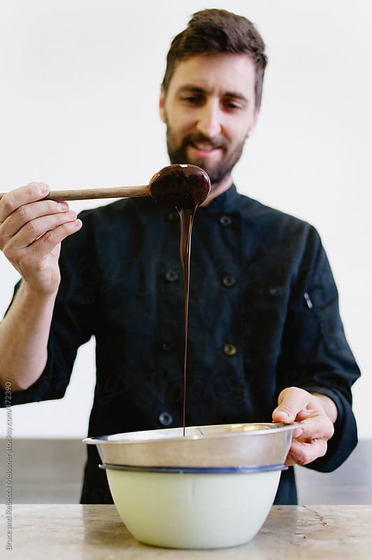 A Man Mixes Chocolate by Bruce and Rebecca Meissner for Stocksy United