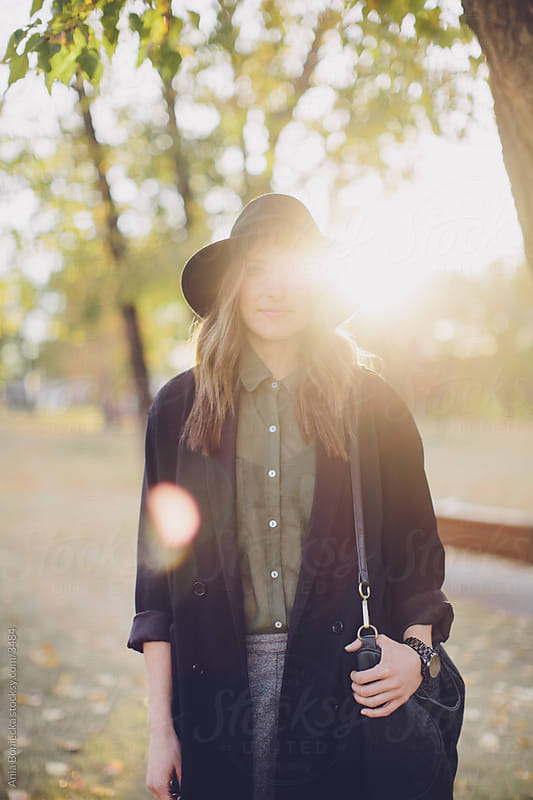 A backlit portrait of a woman in autumn by Ania Boniecka for Stocksy United